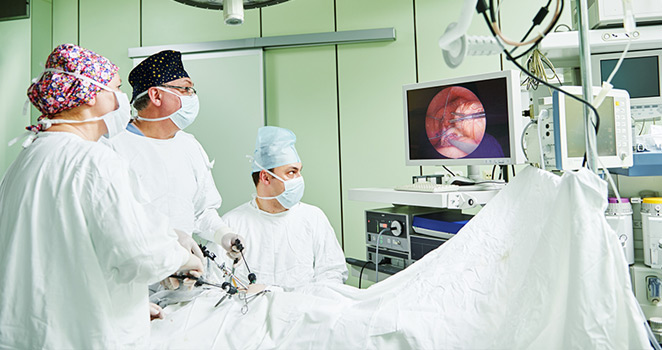 Surgeons watch monitor while performing an advanced procedure