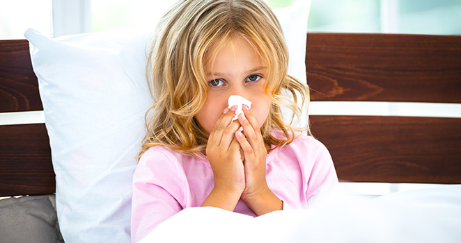 Small girl in bed holding a tissue against her nose
