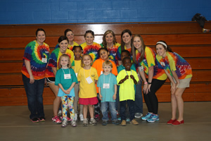 Some of the camp leaders and small children pose for a picture