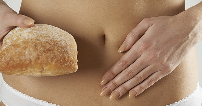Image of a woman holding her abdominal area with one hand and bread in her other hand