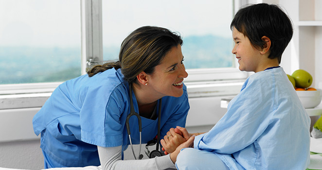 Nurse smiling at a young boy on the exam table