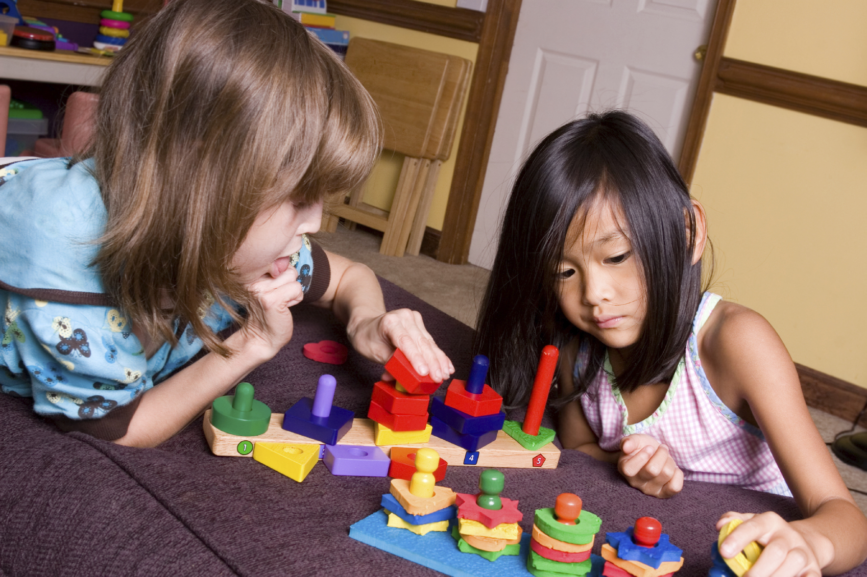 Two children playing with building blocks