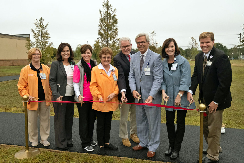 Medical Center of Peach County, Navicent Health staff cut a ribbon to celebrate the opening of their new walking track.