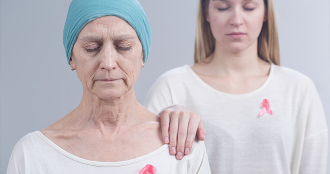 Young woman prays with an older woman who has cancer