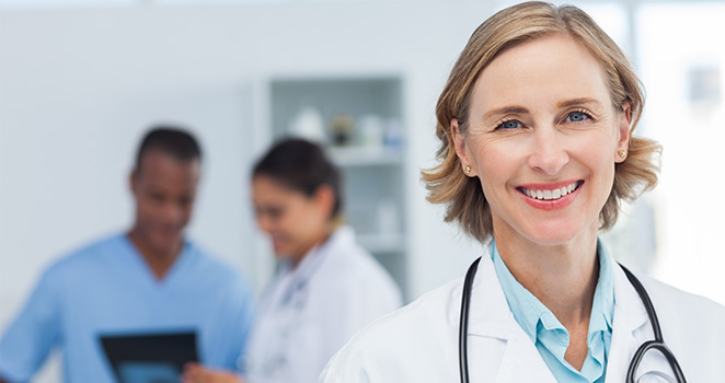 Female doctor standing in the fore-ground smiling and other doctors in the back ground