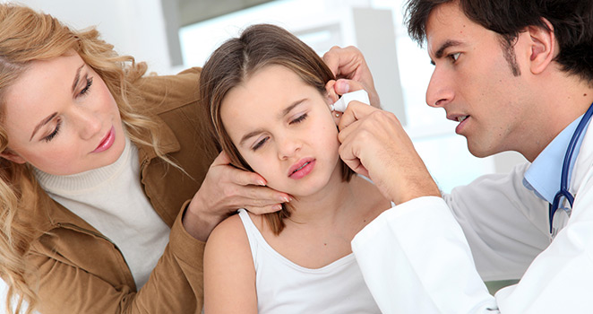 Doctor looking into a young girl's ear