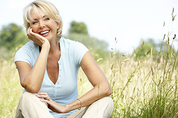 Middle aged woman sitting inthe grass and smiling